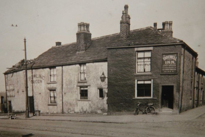 A black and white photo of the streetfront of an old English pub.