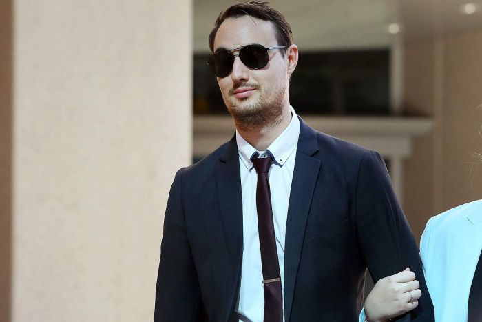 A young man in a suit and sunglasses holding an unseen woman's arm