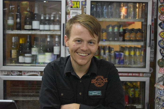 A young man with blonde hair smiles at the camera.  There are bottles of alcohol behind him.