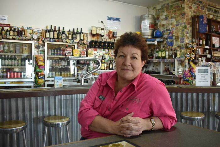A lady in a pink shirt sits at a bar table.  She has blue eyes and is looking at the camera