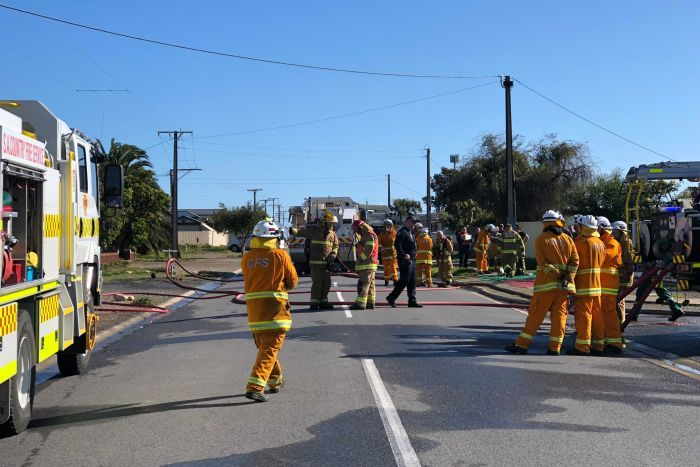 CFS firefighters outside a damaged home.