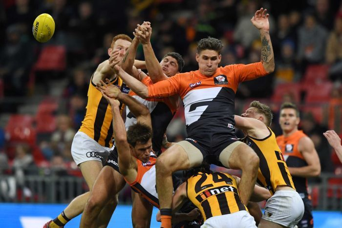 GWS Giants player Rory Lobb falls backwards onto Hawks player jumping for a loose ball