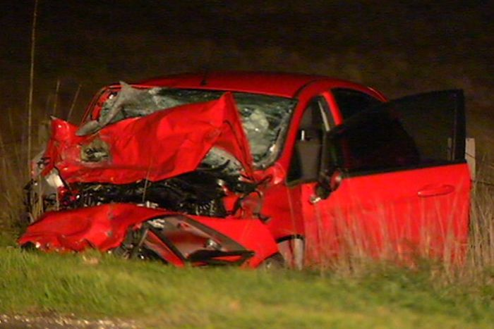 The wreckage of a small red car by the side of the road at the scene of the collision.
