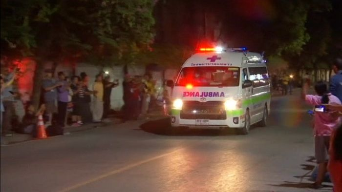Onlookers cheer as ambulances bring the last of those rescued from the cave to hospital