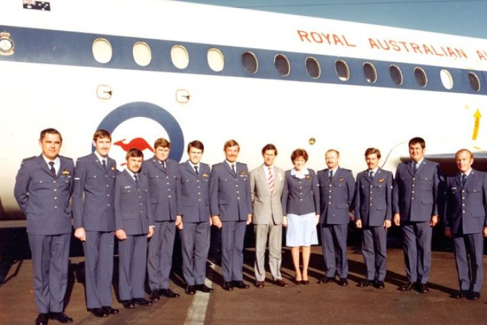 A line of RAAF officers with Prince Charles in the middle. They're standing on a tarmac with RAAF plane in the background.