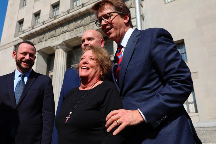 Gail Ingham celebrates the win with her legal team outside the courthouse