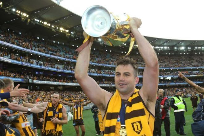 Brian Lake holds the AFL premiership trophy at the MCG after the 2013 grand final.