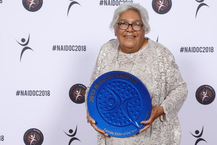 Aunty Lynette Nixon wears a silver white lace dress and black glasses as she holds a large, round, blue award. She is smiling.