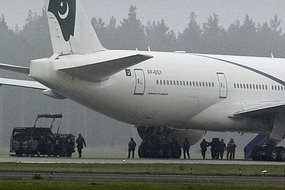 Anti-terrorist officers assemble under a Pakistan International Airlines Boeing 777