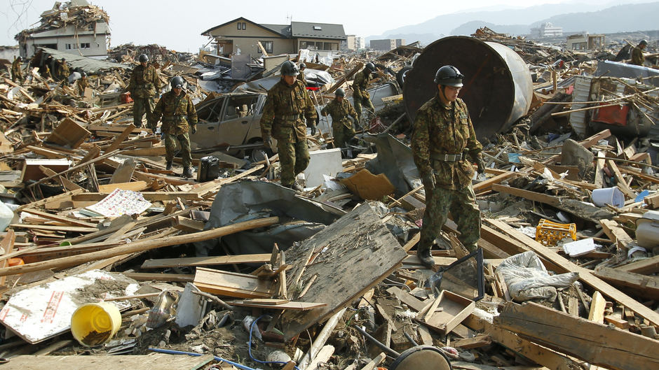 Japanese soldiers search rubble for victims