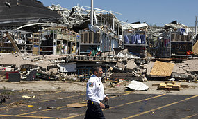 A man surveys the destruction left by a tornado
