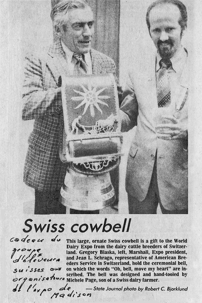 "This large, ornate Swiss cowbell Is a gift to the World Dairy Expo from the dairy cattle breeders of Switzerland. Gregory Blaska, left, Marshall, Expo president, and Jean L. Schrago, representative of American Breeders Service in Switzerland, hold the ceremonial bell, on which the words ""0h, bell, move my heart"" are inscribed. The bell was designed and hand-tooled by Michele Page, son of a Swiss dairy farmer. — State Journal photo by Robert C. Bjorklund"