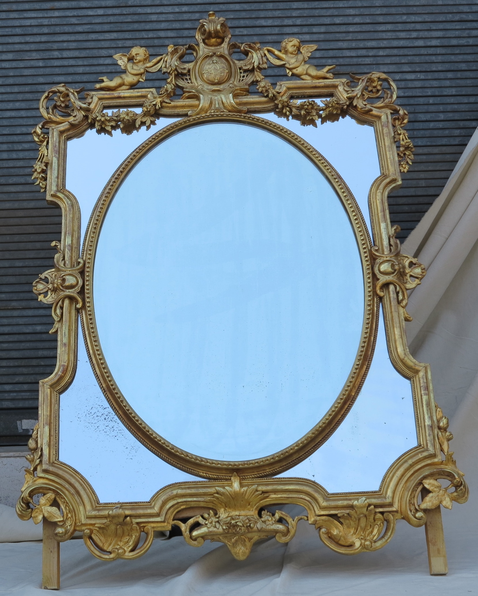 miroir napoleon iii a pare closes et medaillon central ovale biseaute aux anges bois et stuc dore feuilles d or