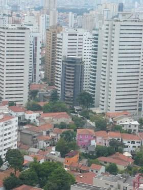 Lustiges Lila Haus vor Wolkenkratzern
