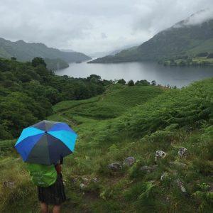 Wanderer mit Ausblick auf Loch Lomond am Fernwanderweg West Highland Way in Schottland