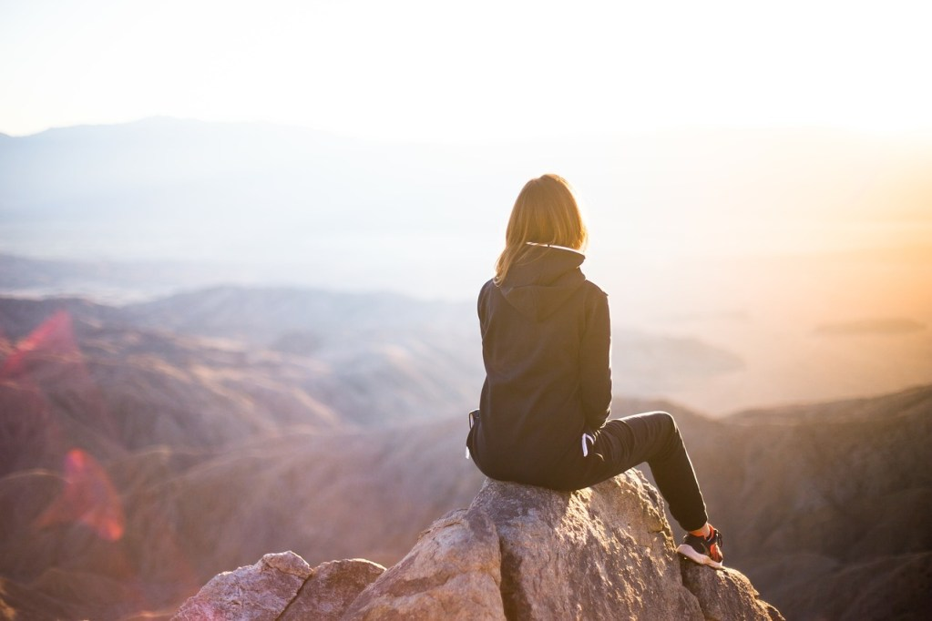 woman looking out over moutain scene at sunset