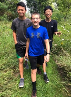 Three smiling boys hiking trail.