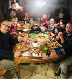 Families taste Raclette cheese around table
