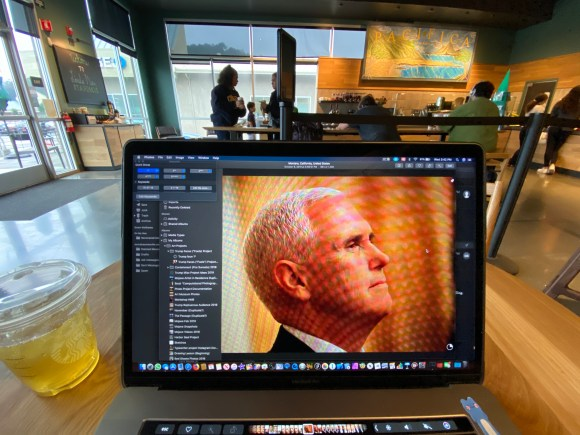 Vice President Pence shown on a laptop screen, the laptop sitting on a table in a coffee shop.