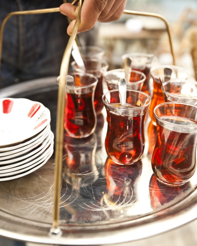A waiter carrying a tray of Turkish tea