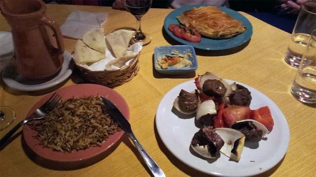 Vorne: Shish-Kebab mit Pilav; Mitte: Hummus mit Fladenbrot; Hinten: Vegetarisches Käse-Gericht