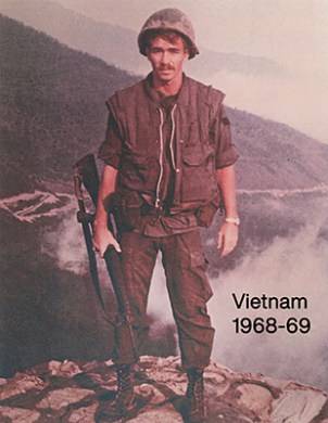 Gregg Cunningham holding rifle. Posing on mountainside in Vietnam, circa 1968 to1969.