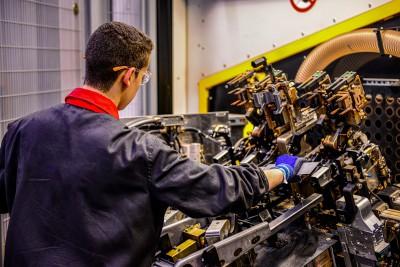Mann an einer Industriemaschine in Werkhalle