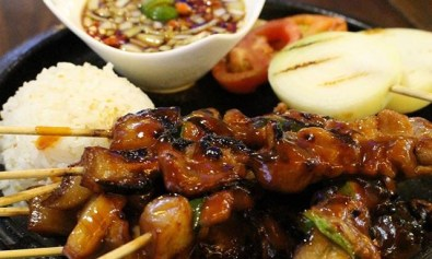 Pork BBQ skewers and rice on sizzling plate