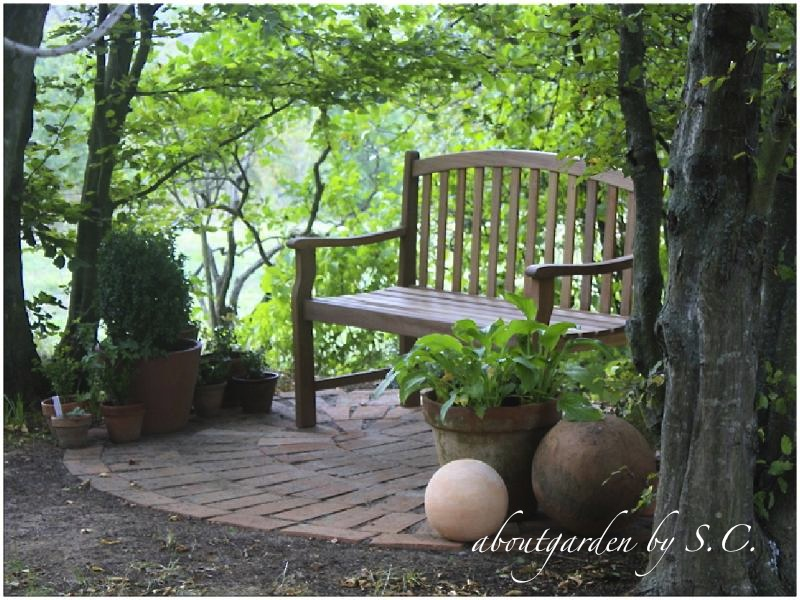 piccolo patio di mattoni con panca e vasi