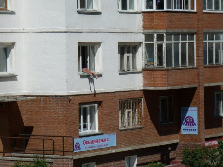 Donna russa prende il sole tutti i giorni fuori dalla finestra