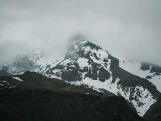 severe snowy mountains under thick clouds