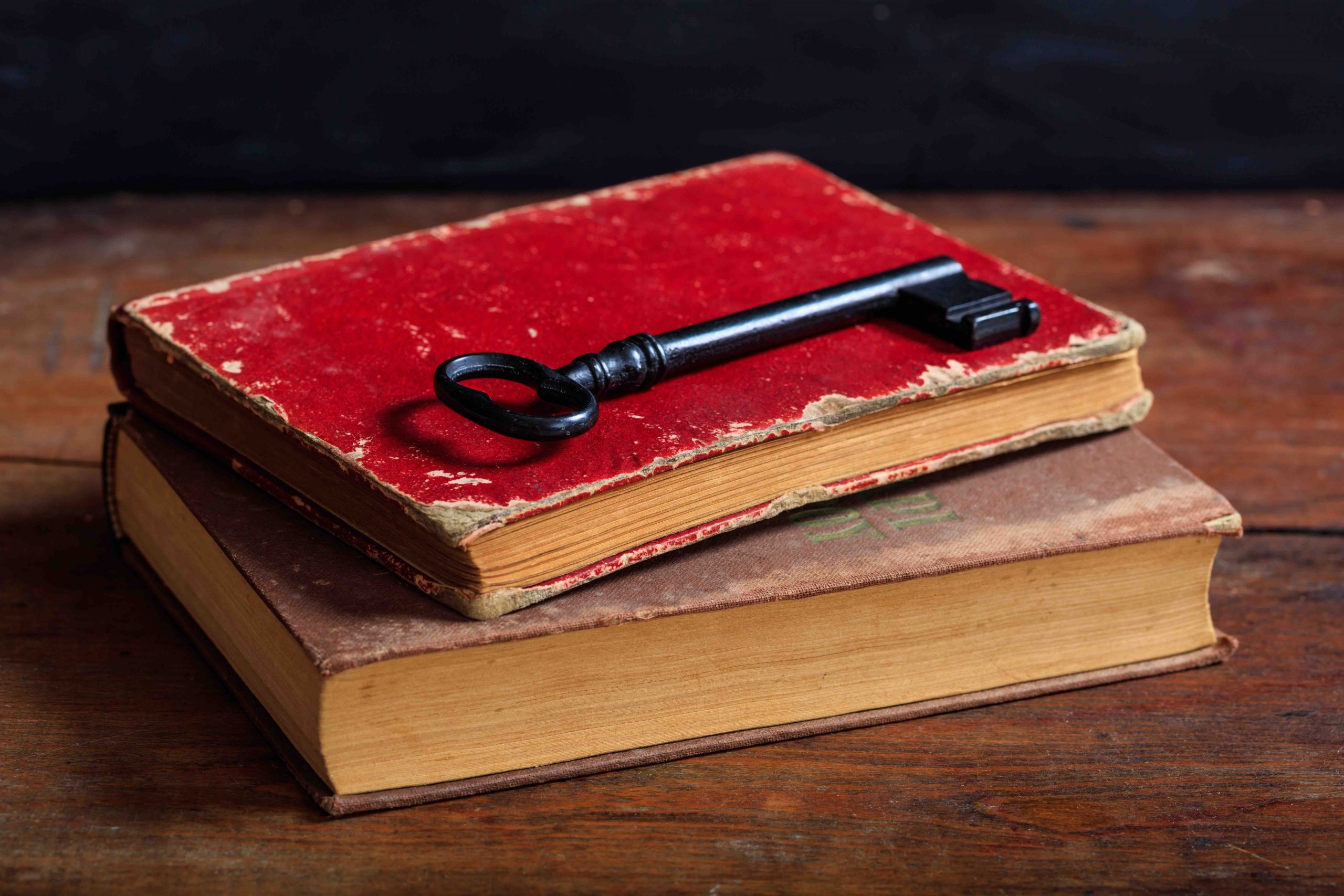 Old books and a key on a wooden desk