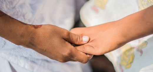 picture of two hands being held from left to right, hands grasped in unity