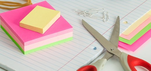 Picture contains a notebook with post-its stacked on top, paperclips, an open pair of scissors, rubberbands grouped and a pen in the background.
