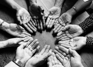 black and white picture of hands held palm up in a circle, all different ages and ethnic representations