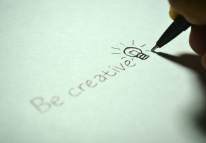 written words 'Be creative' with a handdrawn lightbulb