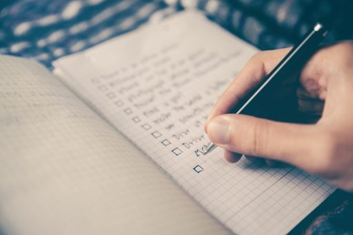 picture of a graph paper notebook a hand writing a list with a black pen
