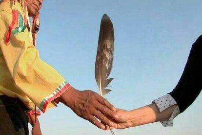 Chief Arvol Looking Horse handing feather