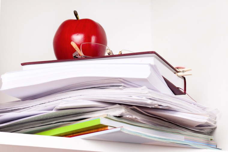 File stack and artificial red apple on the shelves at office close up shot.