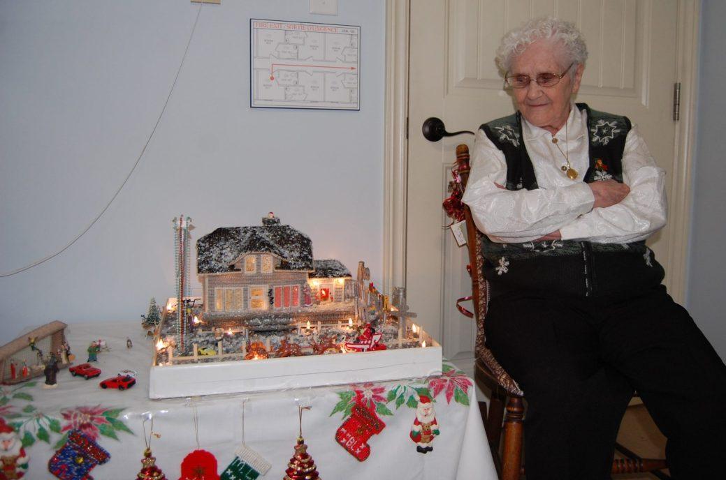 Yolande Lagacé, résidente du Manoir Bienveillance à Beresford, pose à côté d'une reproduction de son ancienne maison qu'elle a fabriquée elle-même - Acadie Nouvelle: Béatrice Seymour