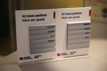 Le petit écriteau qui énonce les multiples langues parlées dans la succursale fait la fierté de David Michaud. - Acadie Nouvelle: Marie Toulgoat