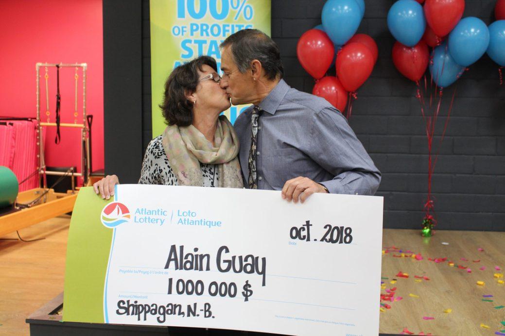 Geneviève Benoît et Alain Guay s'embrassent en tenant le chèque symbolique de Loto Atlantique d'une valeur de 1 million $. - Acadie Nouvelle: Réal Fradette