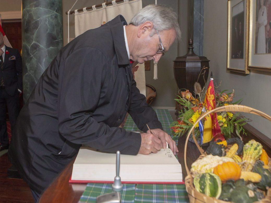 Blaine Higgs signe le livre d'or avant sa rencontre avec la lieutenante-gouverneure du Nouveau-Brunswick, vendredi. - PC