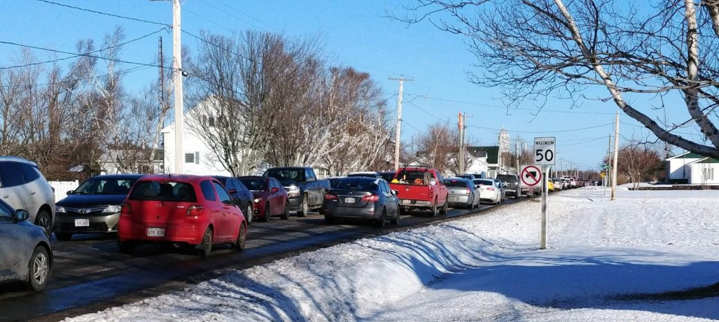 Une longue file de voitures sur le chemin menant au Centre communautaire d'Inkerman. - Acadie Nouvelle: Guillaume Cyr