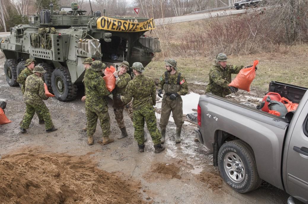 Des membres de l'unité d'intervention du 2e Bataillon du Royal Canadian Regiment chargent des sacs de sable dans les véhicules des résidents de la région de Burton, au sud de Fredericton. - PC