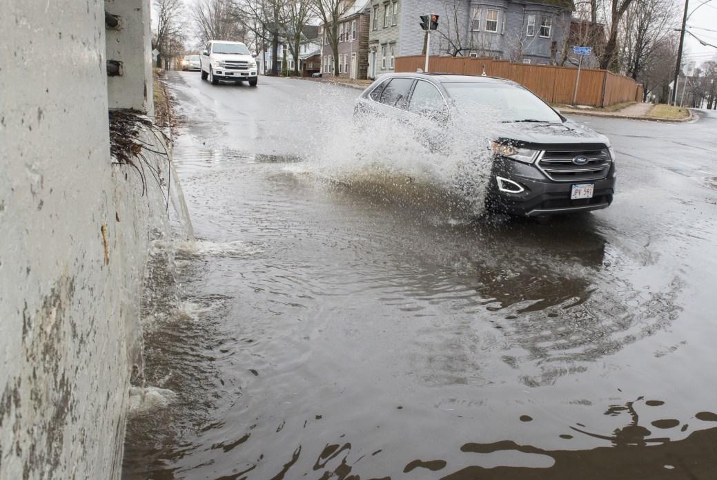 Les eaux de crue du fleuve Saint-Jean se déversent sur un mur de soutènement inondant une rue de Fredericton. - PC