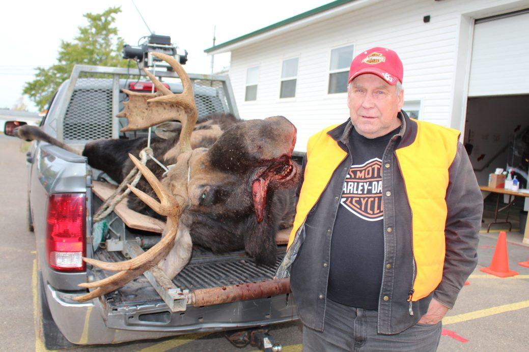 Gilles Thomas pose avec son bel orignal mâle de plus de 600 livres. - Acadie Nouvelle: Réal Fradette