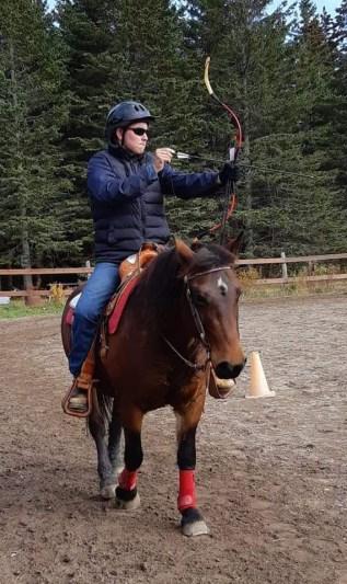 Justin Haché se prépare à tirer à l'arc sur son cheval. - Gracieuseté