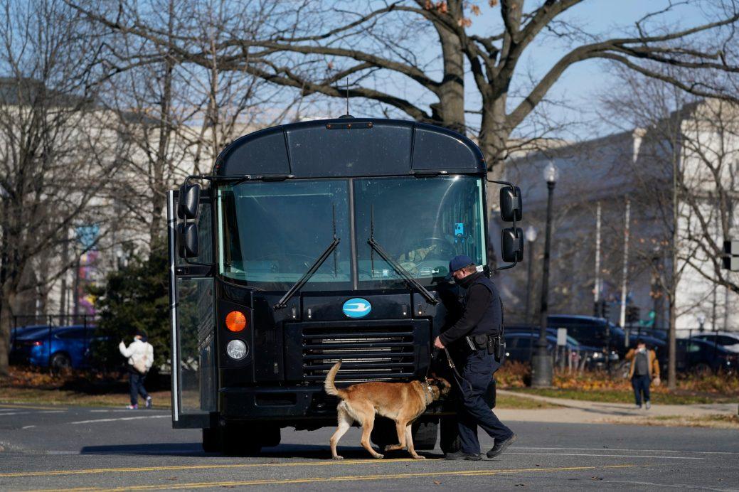 Un chien renifle un bus pour détecter s'il y a des explosifs au Capitole, samedi. - AP