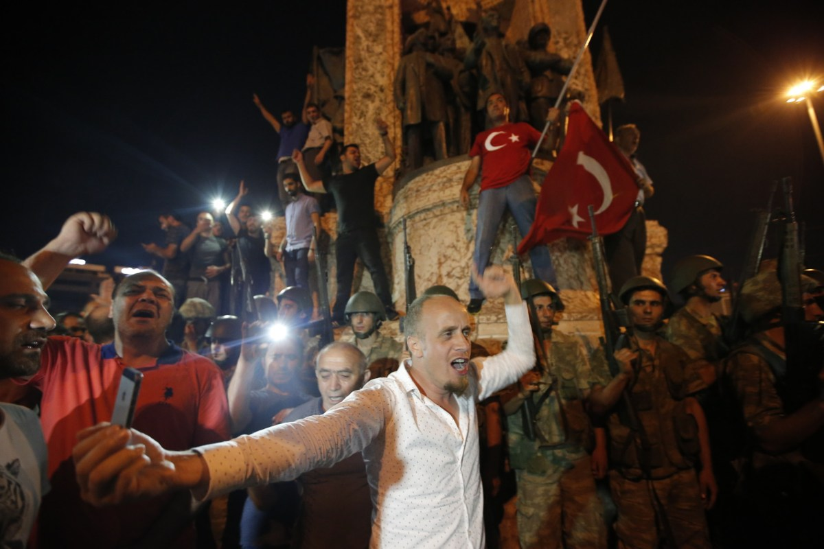 "Supporters of Turkey's President Recep Tayyip Erdogan protest in front of soldiers in Istanbul's Taksim square, early Saturday, July 16, 2016. Turkey's armed forces said it ""fully seized control"" of the country Friday and its president responded by calling on Turks to take to the streets in a show of support for the government. A loud explosion was heard in the capital, Ankara, fighter jets buzzed overhead, gunfire erupted outside military headquarters and vehicles blocked two major bridges in Istanbul. (AP Photo/Emrah Gurel)"
